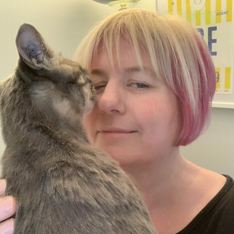 Lady with pink hair being bumped in the face by a grey tabby cat